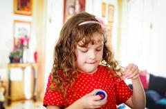 Little girl cutting adhesive tape Stock Photos