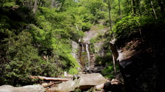 waterfall cascades down steep mountain rock - stock footage