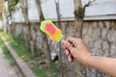 Colorful popsicle in hand. - stock photo
