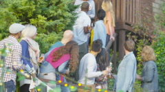 4K Happy group of friends raise beer bottles for a toast at outdoor party - stock footage