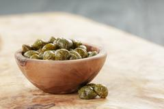marinated capers in bowl on olive board - stock photo