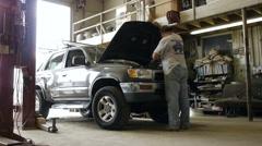 Mechanic repair man closing the hood on a truck - stock footage