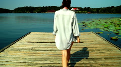 Girl with men's shirt walking on a wooden pier.  Bare foot  on wooden pier. Stock Footage