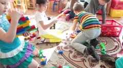 Cute boys and girls have fun while playing toys on the floor of classroom. Rus Stock Footage