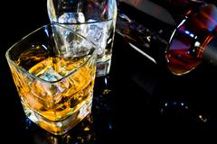 top of view of glass of whiskey near bottle on black table with reflection - stock photo