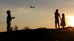 Three children are playing with an airplane toy on sunset. Stock Footage