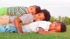 Three children are playing on the glade. They are laughing and having fun. Stock Footage