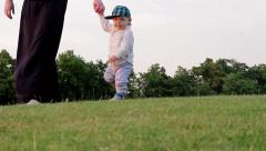 Little boy goes to his mother's hand. Toddler learning to walk. Stock Footage