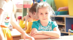 Happy smiling preschool girl communicates with children in daycare center Stock Footage