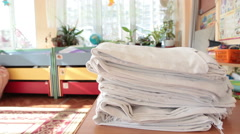 White linen laying on the table while daycare assistant preparing beds for kids  - stock footage
