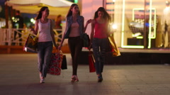 Three friends, girls on street of big city with shopping bags, slow motion. Stock Footage