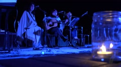 Middle age ladies play guitar and sing poetry at night and candle burn. 4K Stock Footage