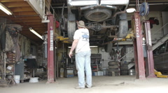 Mechanic shop working on a truck while its being lifted Stock Footage