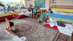 The children lay on a sliding three-tier beds in daycare center during daytime Stock Footage