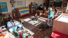 Class in kindergarten, children are playing with toys, woman educator sits Stock Footage