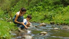Mother with son are launching the toy paper boat - stock footage