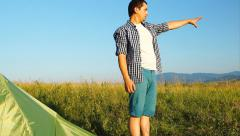 Man stands near a tourist tent and watching far - stock footage