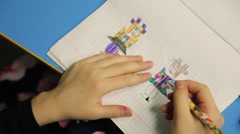 The girl draws a notebook scary dolls. - stock footage