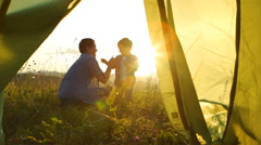 Father with son are playing near a tent on sunset - stock footage