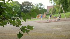 Children playing on the swing in the park: children out of focus Stock Footage
