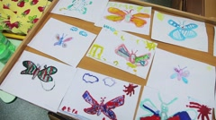 Children draw on the paper paints a butterfly Stock Footage