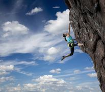 Female rock climber hanging over the abyss - stock photo