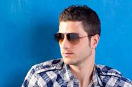 Handsome man with plaid shirt and sunglasses Stock Photos