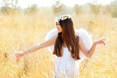 Angel girl in golden field with feather white wings Kuvituskuvat