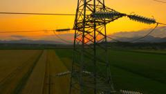 AERIAL: Flying up the high voltage electricity tower at sunset - stock footage