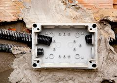 Electrical coil conduit pipe on box embedded in wall Stock Photos