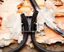 electrical coil conduit pipe on box embedded in wall - stock photo