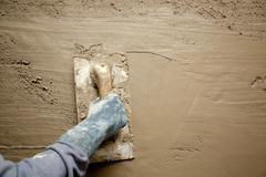 trowel with glove hand plastering cement mortar - stock photo