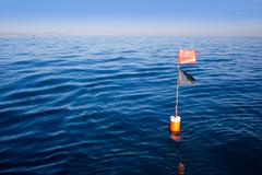 Longliner and trammel net buoy with flag pole - stock photo