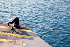 Bollard in port with rope looped around Stock Photos