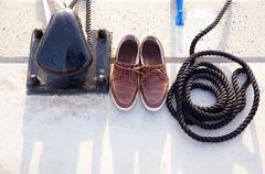Bollard with nautic shoes and rope coil Stock Photos