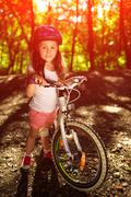 Little girl with bicycle in summer park against sunset Kuvituskuvat