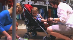 Little cute 3 year old blond girl   trying on shoes in a store - stock footage