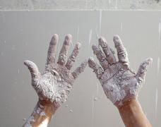 Astist plastering man hands with cracked plaster - stock photo