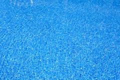 blue tiles pool water texture on summer day - stock photo