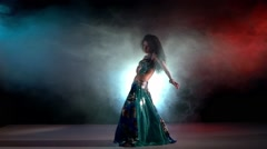 Brunette woman go on performing belly dance movements, on red, blue, smoke, slow Stock Footage