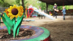 Children's Playground garden with artificial flowers and grass Stock Footage