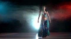 Professional belly dancer in a blue stage costume dancing in smoke, on red, blue Stock Footage