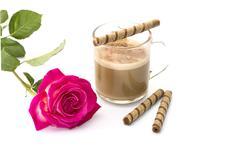 Beautiful scarlet rose and cappuccino with tubular cookies Stock Photos