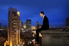 Business man sitting on the rooftop of the building Stock Photos