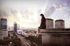 Business woman sitting on building rooftop Stock Photos