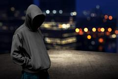 Faceless man in hood on the rooftop - stock photo