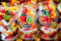 Colorful fruit salad in transparent glasses - stock photo