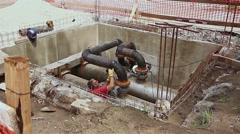 Manhole, metalworker is preparing pipeline node for welding. Stock Footage