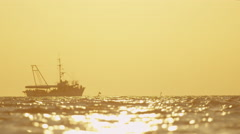 SLOW MOTION: Fishing boat sailing on ocean horizon at sunset Stock Footage