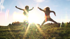 Two girls having fun jumping in the sunset Stock Footage